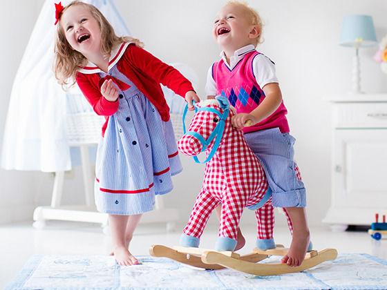 Kinder spielen in ihrem Kinderzimmer auf Teppichboden